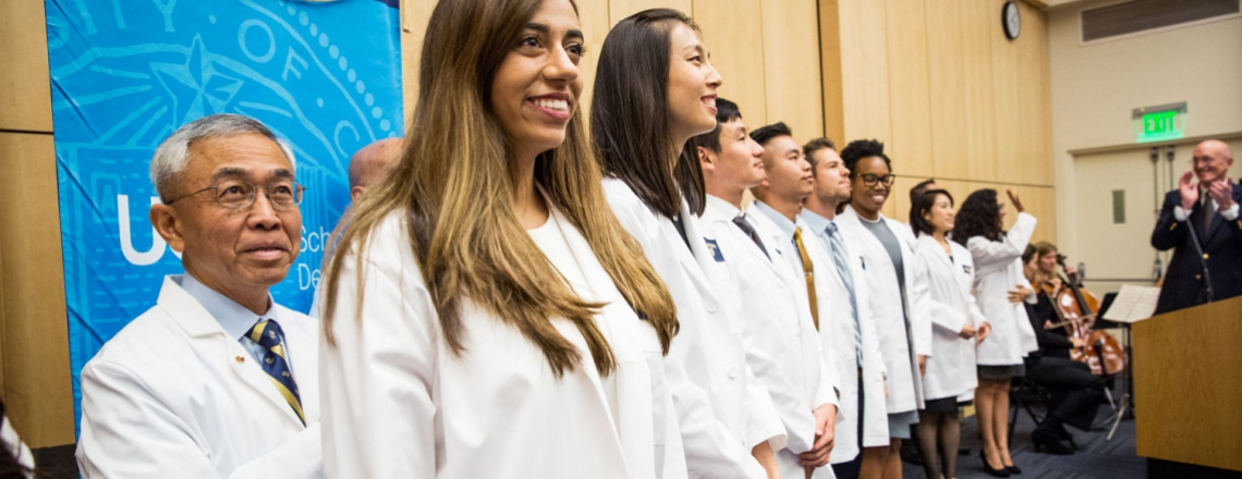 UCSF dental students line up on stage during their white coat ceremony