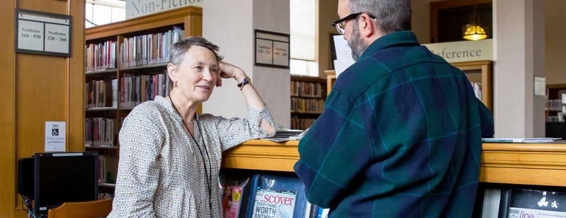 Librarian Valerie Reichert talks to a library patron