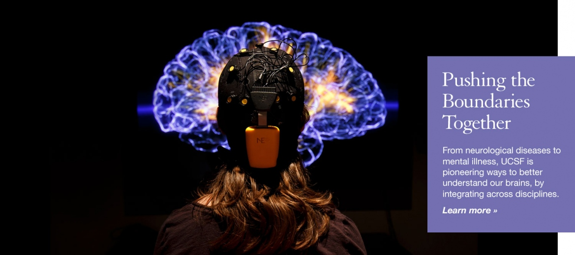 woman wearing a brain sensor cap looks at a digital brain image