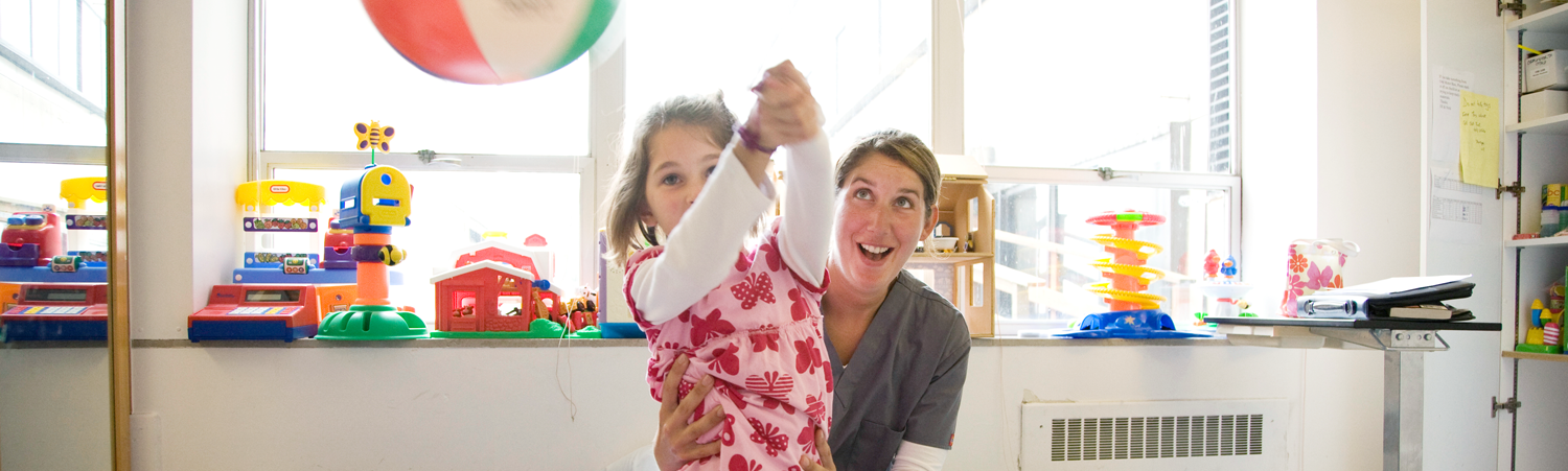 A UCSF physical therapist helps a pediatric patient balance while hitting a beach ball