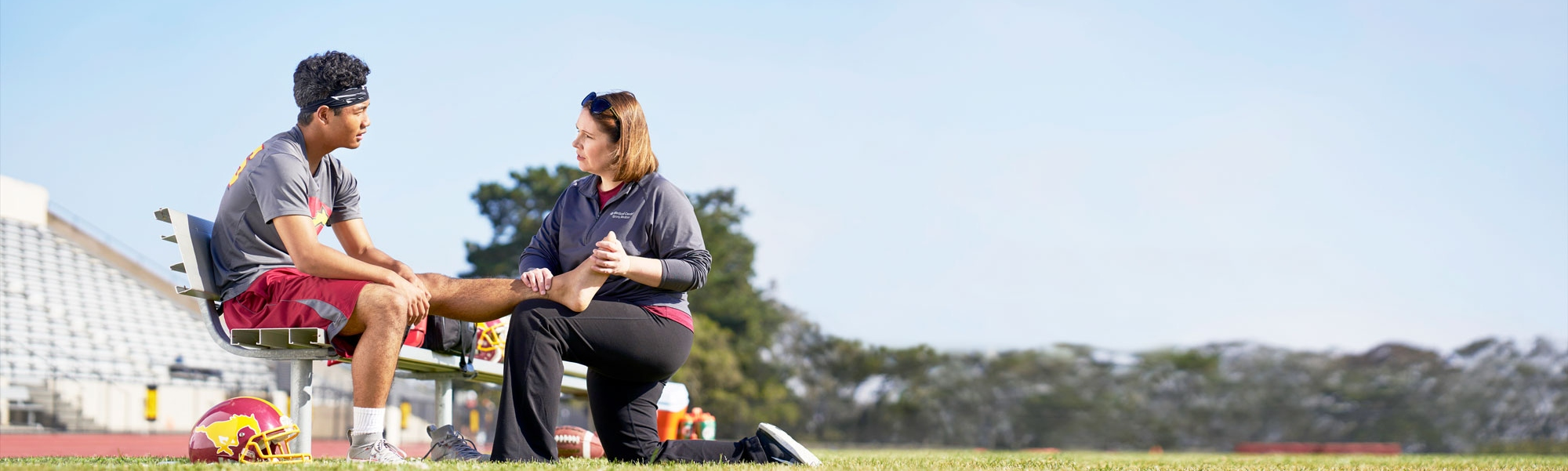 UCSF doctor helping a teen athlete with his leg on the field