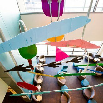 A colorful mobile made of geometric shapes hangs above the lobby of the Ron Conway Family Gateway Medical Building