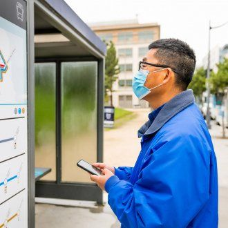 A man looks at the shuttle schedule posted on the bus stop