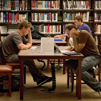 Several people read books set out on a table in the FAMRI Library