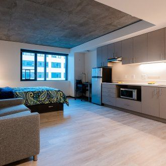 A spacious studio unit with a concrete ceiling, kitchen, and living area