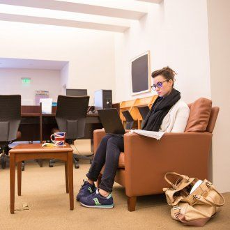 A student sits in an armchair with her laptop in the FAMRI Library