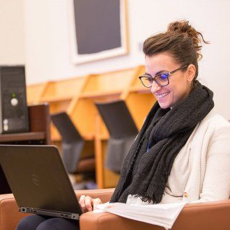 Postdoc Benedetta Milanini laughs as she looks at her laptop in the FAMRI Library