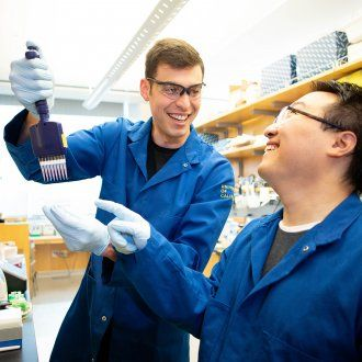 Reuben Saunders and Dian Yang laughing while Reuben holds up a pipette