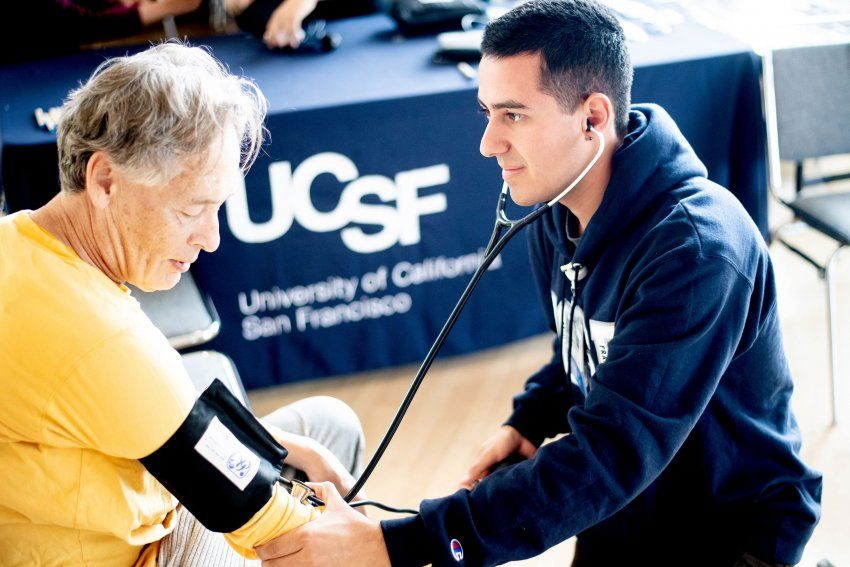 Medical student measuring woman's blood pressure.