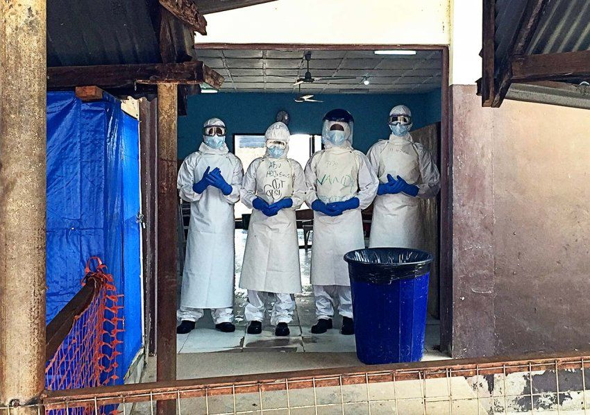 Medical workers in head-to-toe protective suits stand in a doorway of a run-down building with an orange makeshift fence and blue tarp hanging.