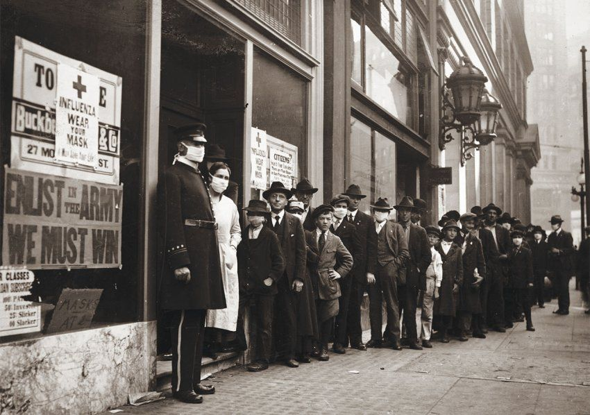 "Line of people waiting for flu masks at 30 Montgomery Street, San Francisco, 1918. The man in uniform and the nurse in the doorway are wearing masks, as are a few of those in line. A sign on the window bearing the Red Cross logo reads: ""Influenza. Wear Your Mask."" A sign underneath reads: ""Enlist in the Army. We Must Win."""