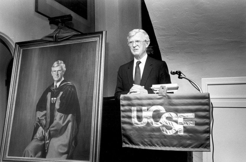Philip Lee standing at UCSF podium next to his portrait